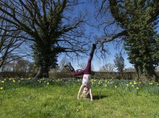 Girl cartwheels in front of daffodils in spring at RHS Garden Wisley.