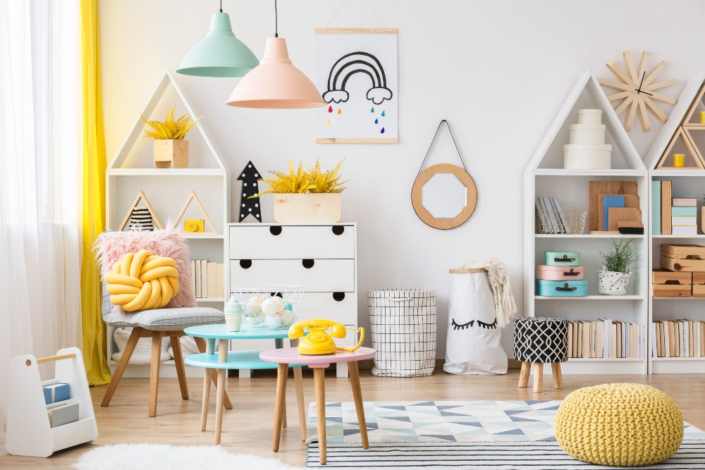 Yellow pouf near pink table with a phone in pastel kid's playroom interior with poster on white wall